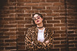 Stylish portrait of young serious woman with crossed arms wearing trendy leopartd print faux fur coat, fashion sunglasses, posing on red brick wall texture grunge background