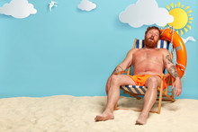 Relaxed Bearded Man Sleeps On His Deck Chair, Poses On Beach, Has Red Sunburned Skin, Sunbathes And Tans, Has Summer Vacation And Holiday Travel, Beautiful Sea View In Background. People And Rest