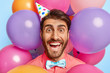Leinwandbild Motiv Lucky cheerful man with happy look, makes photo against party attributes, wears cone paper hat, elegant bowtie and rosy shirt, poses with colorful balloons in background. Special occasion concept
