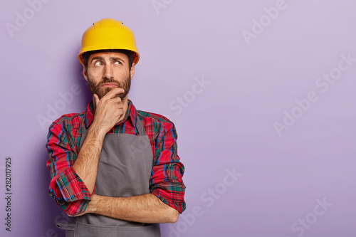 Obraz Thoughtful man builder construction touches chin, thinks over new idea for building, works as repairman, wears yellow protective helmet, checkered shirt and apron. Industry and repairing concept - fototapety do salonu