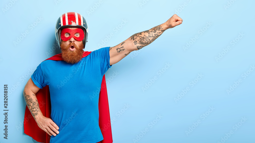 Fototapeta Stupefied emotive man with ginger beard being cartoon character, keeps arm in flying gesture, wears protective headgear, blue t shirt and red cloak, has shocked expression, saves our universe