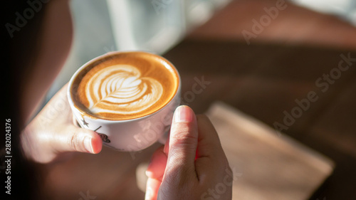 Fotografie, Obraz  Woman with cup of coffee latte art at cafe