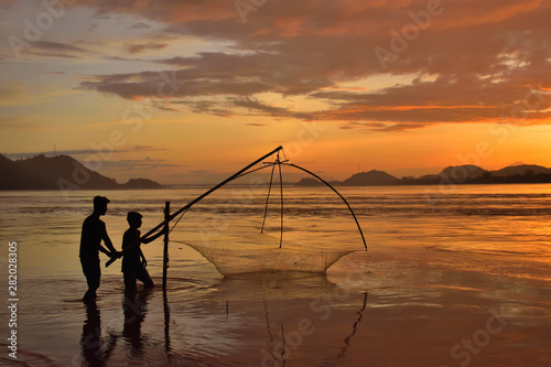 Photo People fishing in river brahmaputra during sunset.