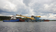 Pusher Ship Carries Barge And Dredger On The River On Stormy Sky Background, Logistics Of Cargo Transportation By Water Transport