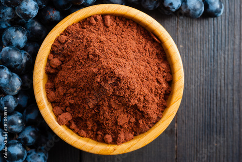 Fotografie, Obraz  grounded grape seed grist and fruits on black wood table