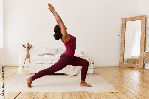 Foto  Attractive flexible young dark-skinned female in sportswear training indoors, do