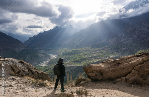 a man with backpack  standing on top of mountain with sunlight through cloudy sky Canvas Print
