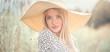 Leinwandbild Motiv Beautiful model girl posing on a field, enjoying nature outdoors in wide brimmed straw hat. Beauty blonde young woman with long straight blond hair closeup portrait