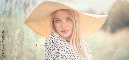 Vászonkép Beautiful model girl posing on a field, enjoying nature outdoors in wide brimmed straw hat