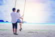 Romantic couple relaxing together on rope swing at the beach, Love and honeymoon concept.