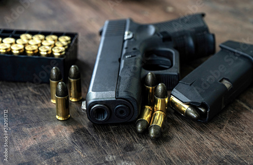 Fotografie, Obraz Guns and ammunition on the wooden table, top view and free space for entering your text