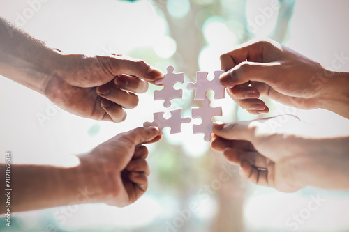 Photographie  Closeup hand of business people connecting jigsaw puzzle with sunlight effect, B