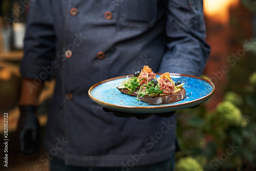 Fotografía  delicious raw beef tartare on bruschette, the dish is held in hand by a cook in a blue uniform