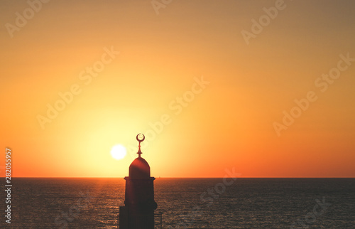 Montage in der Fensternische Melone minaret tower with Islamic crescent religion sign architecture silhouette on atmospheric sunset above Mediterranean sea scenic landscape idyllic background with empty space for copy or text
