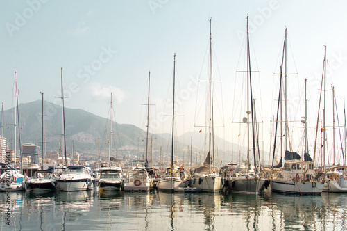 Fototapety, obrazy: Sailboats and yachts in the dock reflected in the water with the city and mountains in the background. Landscape of Costa del Sol (Fuengirola), Spain.