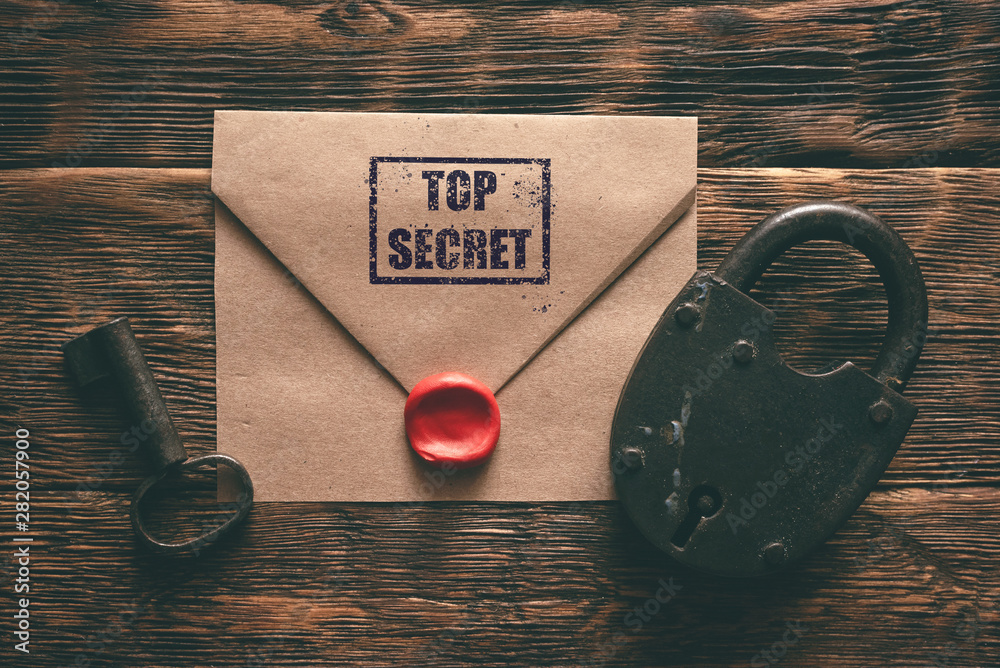 Fototapeta Top secret documents in envelope, rusty padlock and a key on a wooden table flat lay background. Confidential information concept.