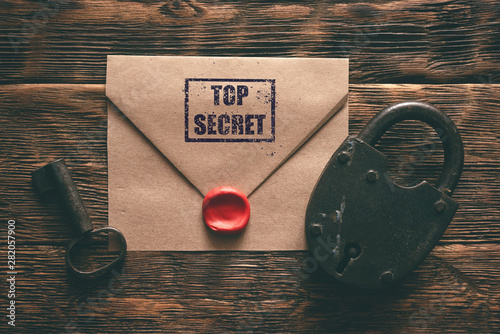 Photo Top secret documents in envelope, rusty padlock and a key on a wooden table flat lay background
