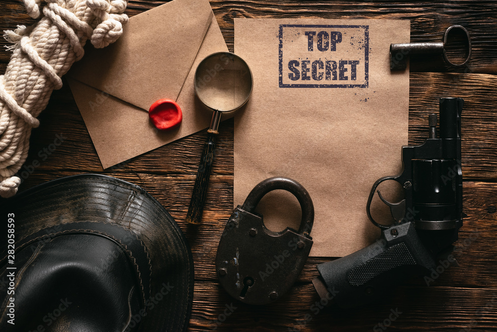 Fototapeta Top secret information mockup, leather hat, weapon, magnifying glass and rope on a wooden table of secret service agent flat lay background.