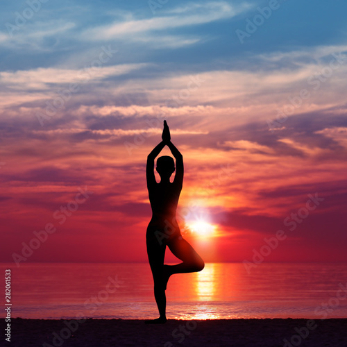 Fototapeta Silhouette of Woman Meditating in Yoga pose by the Sea at Sunset. Nature Meditation Concept. Low key photo. relax time obraz na płótnie