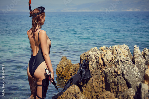 Photo sur Toile Chasse sexy woman with fins and crossbow is preparing to hunt for fish