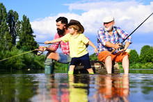 Fishing Became A Popular Recreational Activity. Grandfather With Son And Grandson Having Fun In River. Men Hobby. Family Fishermen Fishing With Spinning Reel.