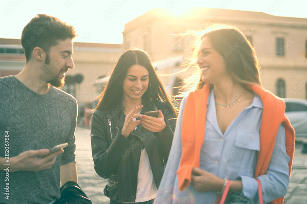 Fototapety, obrazy: Group of young people walking and having fun time joking together and using smartphones outdoors. Young people lifestyle using smartphones concept