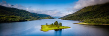 Aerial View Of Loch Leven Near Kinlochleven And Glen Coe In The Argyll Region Of The Highlands Of Scotland With A Green Island In The Foreground And Calm Blue Waters With Misty Mountains