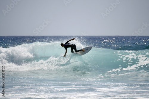 Young pro surfer surfs a big barrel wave in popular surf spot in breathtaking Fototapete