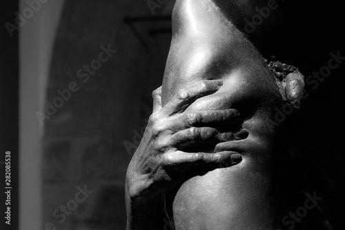 Obraz Dettaglio di una statua in bianco e nero che ritrae una mano che stringe la gamba di un uomo nudo - fototapety do salonu