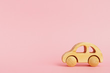Wooden Baby Car On A Pink Pastel Background With Copyspace.