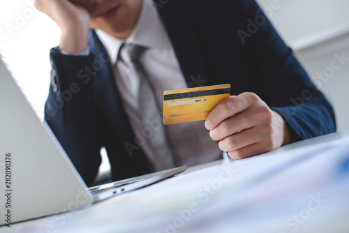 Fényképezés Man in a suit holding a credit card in hand
