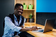 Afro-American student working from home using laptop at kitchen.