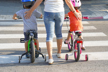 Mother Goes Pedestrian Crossing With Children On Bicycles. A Woman With Children Crossing The Road In The City. Back View.