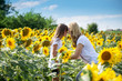canvas print picture - Carefree daughter enjoying with her mother among sunflowers