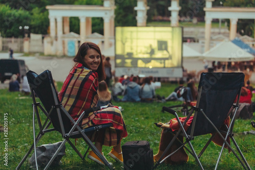 Wallpaper Mural woman eating chips sitting in camp-chair looking movie in open air cinema