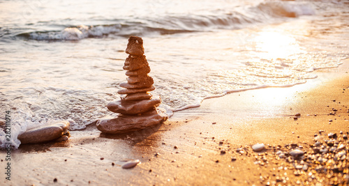 Photo sur Plexiglas Zen pierres a sable stones of the pyramid on the beach symbolize the concept of Zen, harmony, balance.