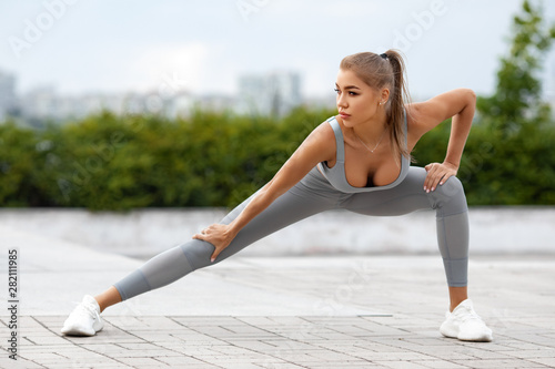 Obraz na plátně  Fitness woman stretching and warming up for her training outdoors