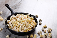 Prepared Popcorn In Frying Pan, Corn Seeds In Bowl And Corncobs On Kitchen Table.Air Salty Popcorn. Salt Popcorn On The Wooden Background . Chees .Popcorn Texture