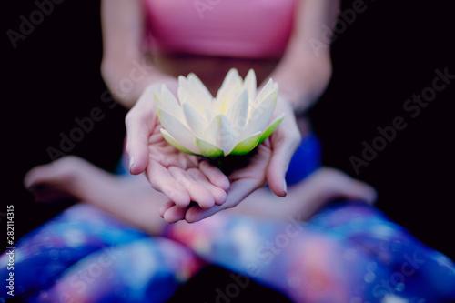 Yoga woman holding lotus blossom.
