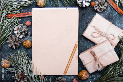 Valokuva  Christmas background with blank notebook surrounded by Christmas decorations