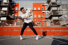 Young Guy Dressed In Jeans And T-shirt Is Dancing Modern Dance In The Street On The Background Of Urban Buildings In The Warm Day