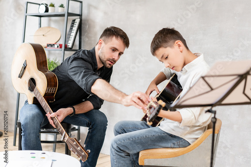 Fotografie, Tablou Adult man explains his son, who learn to play guitar, how to play studied chord correctly