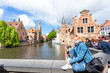 Leinwanddruck Bild - A young woman with the flag of Belgium in her hands is enjoying the view of the canals in the historical center of Bruges.