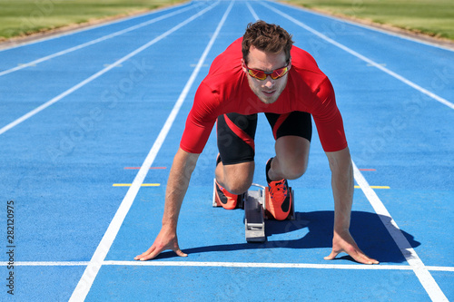 Sport athletics track and field stadium fitness athlete starting race at running tracks ready to run. Runner man going running outside on blue track lanes.