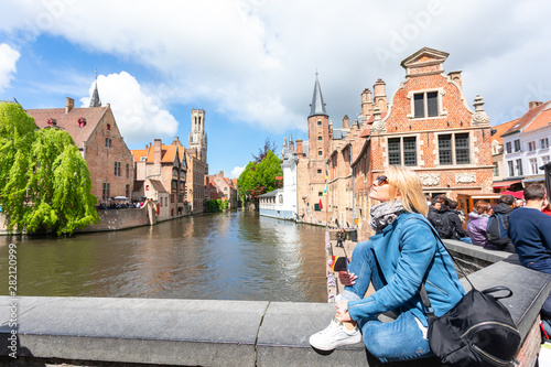 Poster Bridges A young woman with the flag of Belgium in her hands is enjoying the view of the canals in the historical center of Bruges.