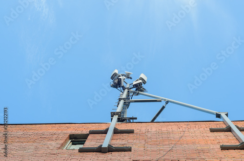 Cellular antenna on the roof of a brick house on blue sky background Fototapet