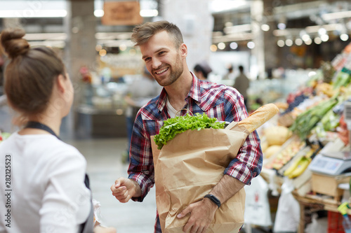 Waist up portrait of handsome young man talking to sales assistant while grocery shopping in supermarket, copy space