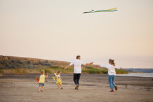 Happy Family, Father And Mother And Two Children Launch A Kite On Nature At Sunset.