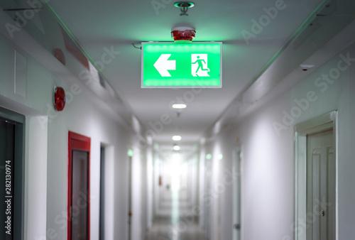 hallway in apartment with , door rooms in dorm Fire exit green light sign Fototapeta