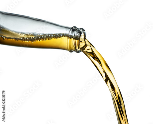 Stop action closeup of amber beer pouring from clear bottle on white background Canvas Print